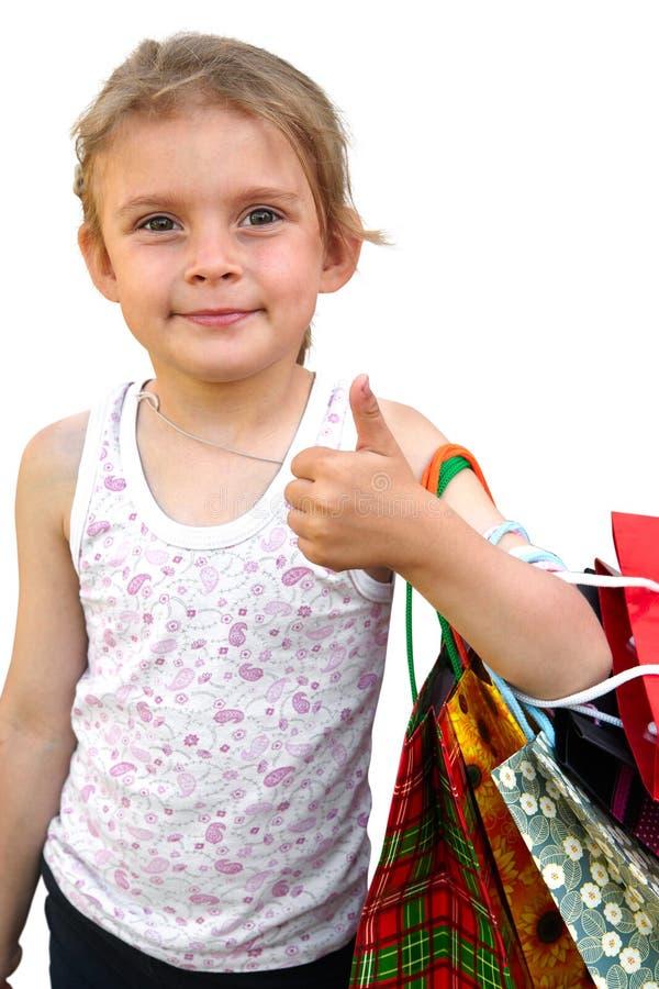 Μικρό κορίτσι με τις τσάντες αγορών στο άσπρο υπόβαθρο Εντάξει στοκ εικόνα
