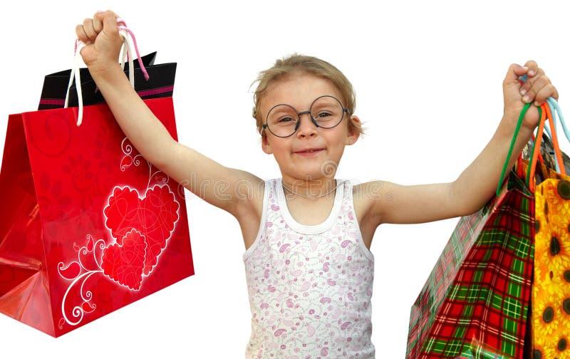 Μικρό κορίτσι με τις τσάντες αγορών στο άσπρο υπόβαθρο στοκ φωτογραφίες