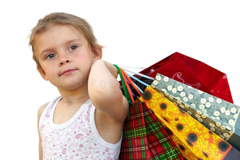 Μικρό κορίτσι με τις τσάντες αγορών στο άσπρο υπόβαθρο στοκ φωτογραφία με δικαίωμα ελεύθερης χρήσης