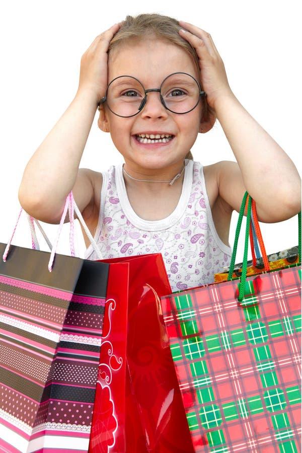 Μικρό κορίτσι με τις τσάντες αγορών στο άσπρο υπόβαθρο στοκ εικόνα με δικαίωμα ελεύθερης χρήσης