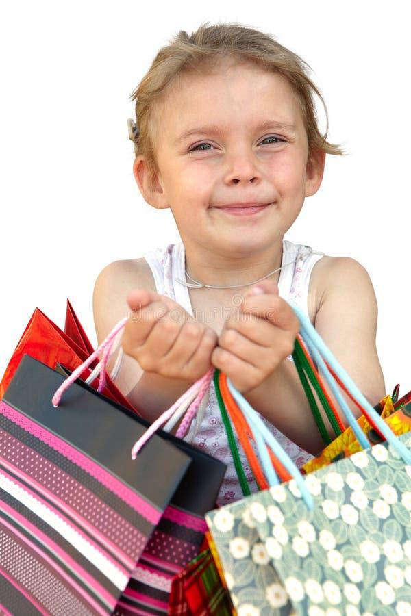 Μικρό κορίτσι με τις τσάντες αγορών στο άσπρο υπόβαθρο στοκ εικόνες