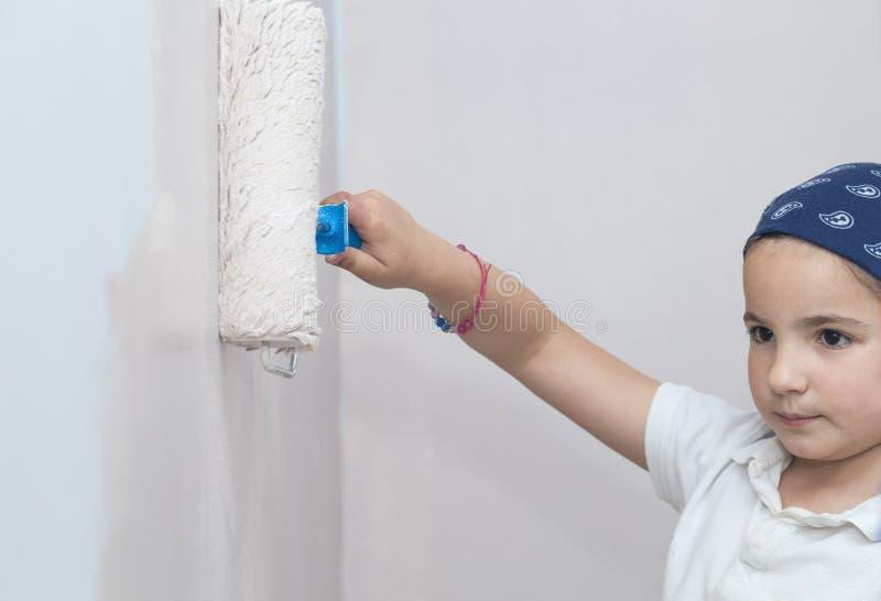 Μικρό κορίτσι με τον κύλινδρο χρωμάτων υπό εξέταση στοκ εικόνα