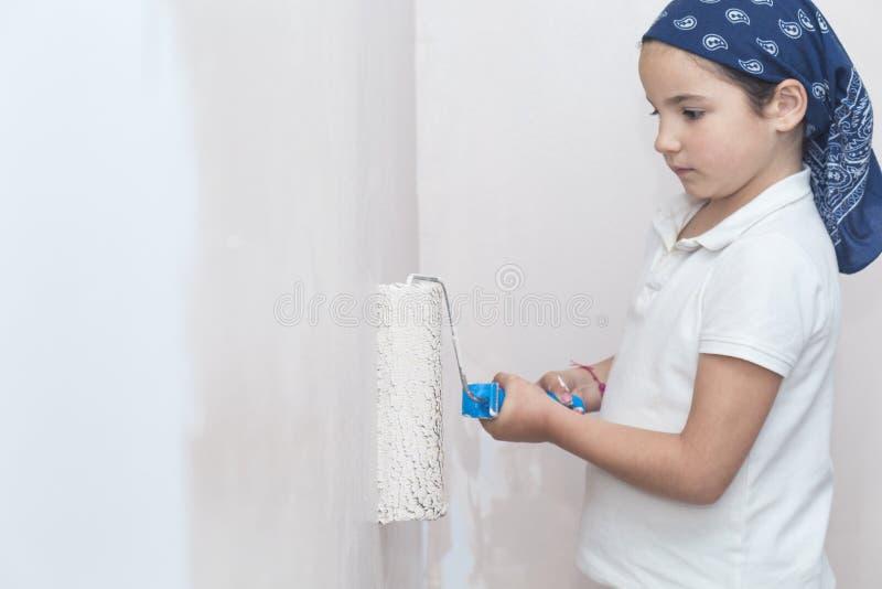 Μικρό κορίτσι με τον κύλινδρο χρωμάτων υπό εξέταση στοκ φωτογραφίες