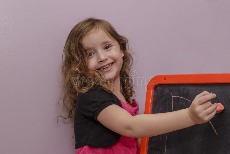 Μικρό κορίτσι με τον πίνακα κιμωλίας στοκ εικόνα