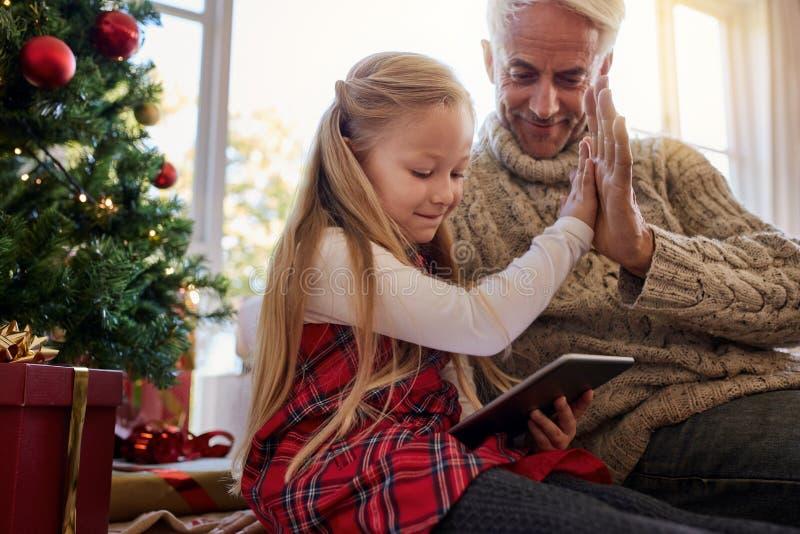 Μικρό κορίτσι με τον παππού που χρησιμοποιεί την ψηφιακή ταμπλέτα στο σπίτι στοκ εικόνες