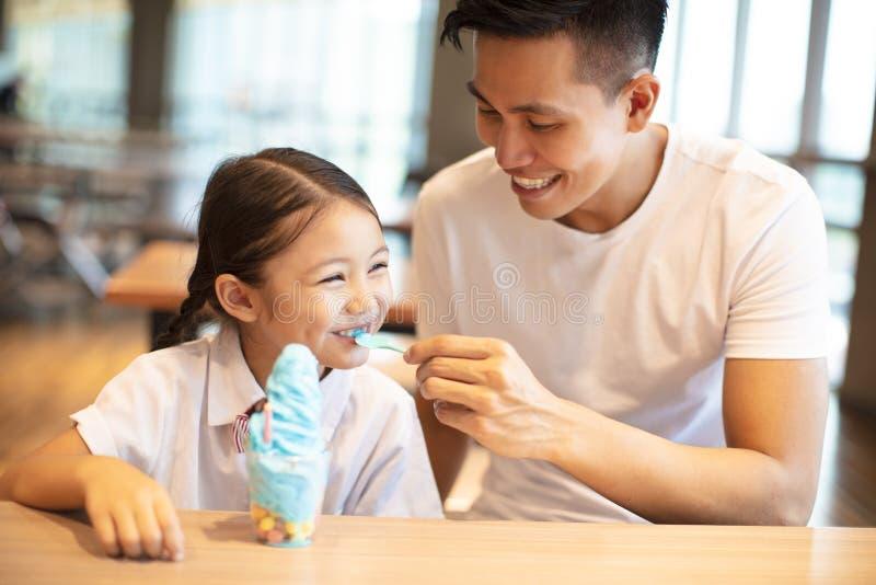 Μικρό κορίτσι με τον πατέρα που τρώει το παγωτό στοκ εικόνες