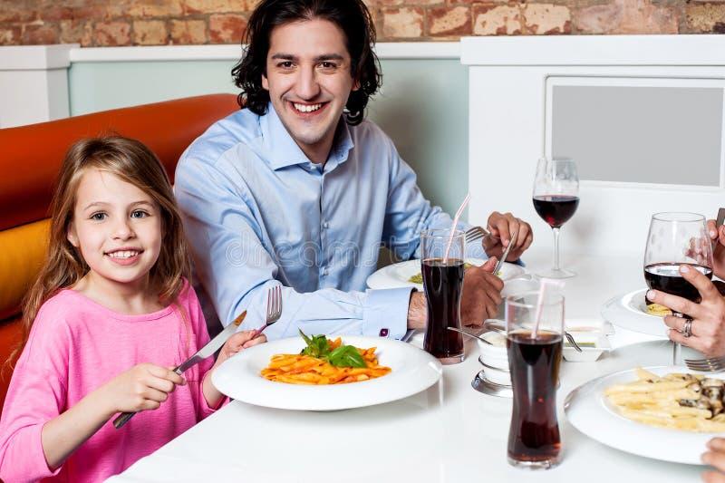Μικρό κορίτσι με τον πατέρα της σε ένα εστιατόριο στοκ εικόνες