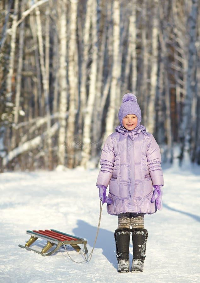 Μικρό κορίτσι με το έλκηθρο το χειμώνα στοκ φωτογραφία
