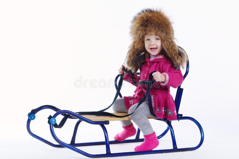 Μικρό κορίτσι με το έλκηθρο στο άσπρο υπόβαθρο στοκ φωτογραφία