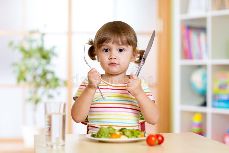 Μικρό κορίτσι με το δίκρανο και μαχαίρι έτοιμο να φάει στοκ φωτογραφίες