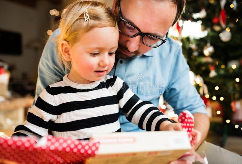 Μικρό κορίτσι με το ανοίγοντας χριστουγεννιάτικο δώρο πατέρων της στοκ εικόνες