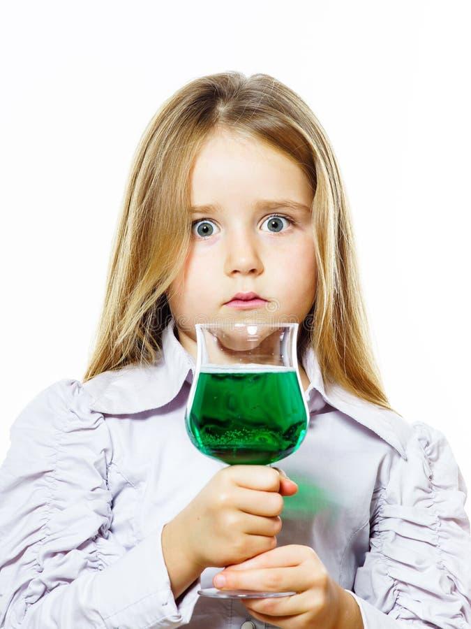 Μικρό κορίτσι με το γυαλί του ζωηρού πράσινου υγρού, ίσως δηλητήριο στοκ εικόνες