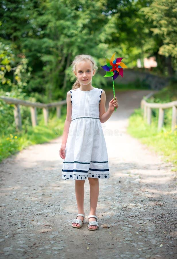 Μικρό κορίτσι με το ζωηρόχρωμο pinwheel στοκ εικόνες με δικαίωμα ελεύθερης χρήσης
