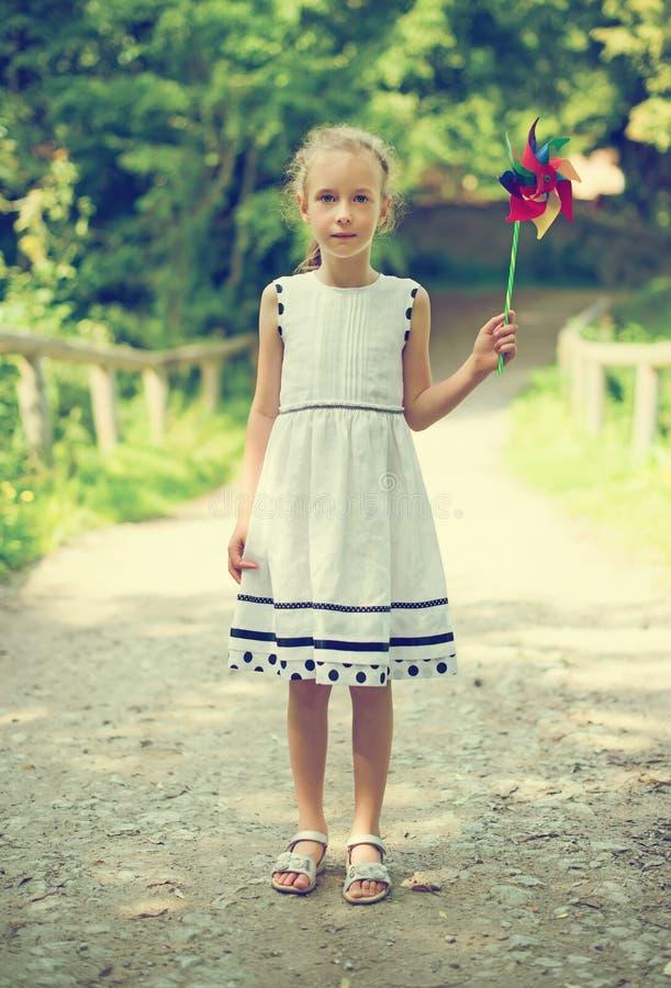 Μικρό κορίτσι με το ζωηρόχρωμο pinwheel στοκ φωτογραφία