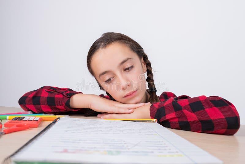 Μικρό κορίτσι με το λυπημένο βλέμμα που εξετάζει το σημειωματάριο εργασίας στο σχολείο στοκ εικόνα