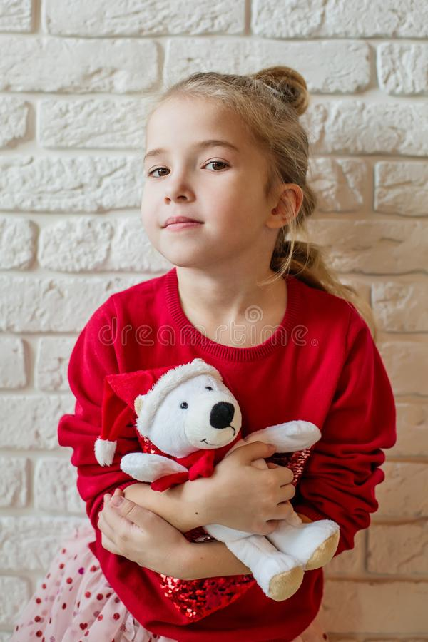 Μικρό κορίτσι με το παιχνίδι αρκούδων μπροστά από τα Χριστούγεννα στοκ φωτογραφίες