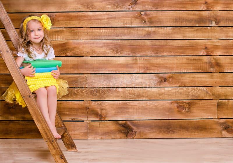 Μικρό κορίτσι με το σωρό των βιβλίων που κάθεται στη σκάλα στοκ φωτογραφία με δικαίωμα ελεύθερης χρήσης