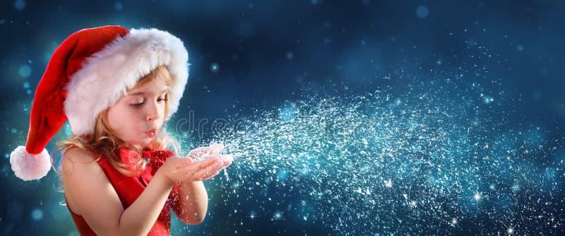 Μικρό κορίτσι με το φυσώντας χιόνι καπέλων Santa στοκ φωτογραφίες