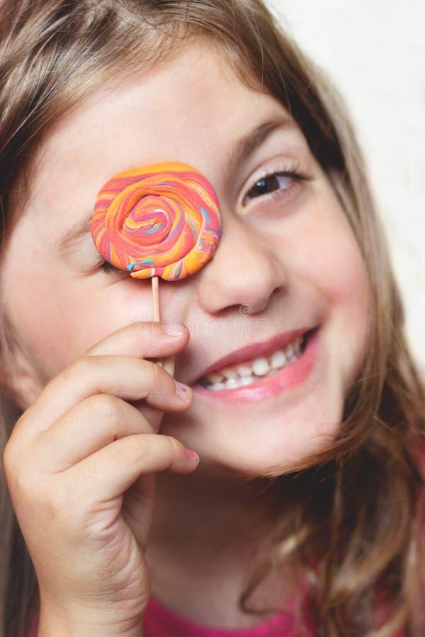 Μικρό κορίτσι με το lollipop πέρα από το μάτι της, κάνοντας τα πρόσωπα και έχοντας τη διασκέδαση στοκ φωτογραφία