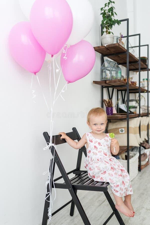 Μικρό κορίτσι με το lollipop στην όμορφη συνεδρίαση φορεμάτων στην καρέκλα με τα ρόδινα μπαλόνια στοκ εικόνες