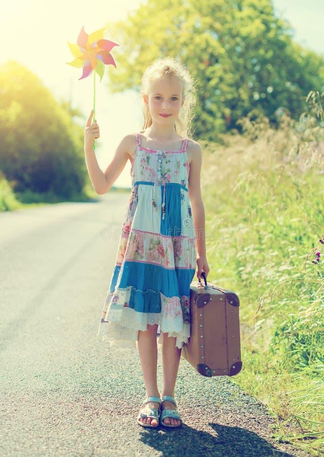 Μικρό κορίτσι με το pinwheel στον αγροτικό δρόμο στοκ φωτογραφία