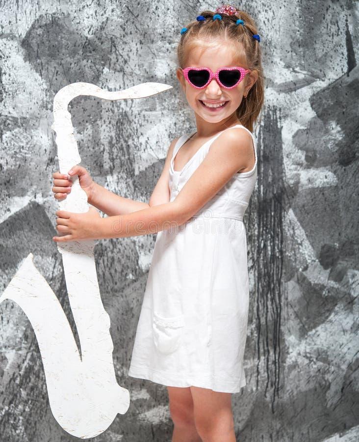 Μικρό κορίτσι με το saxophone της στοκ φωτογραφία