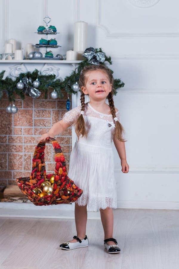 Μικρό κορίτσι με δύο πλεξίδες που στέκονται κοντά σε ένα χριστουγεννιάτικο δέντρο Κρατά ένα καλάθι με τα παιχνίδια στοκ φωτογραφία με δικαίωμα ελεύθερης χρήσης