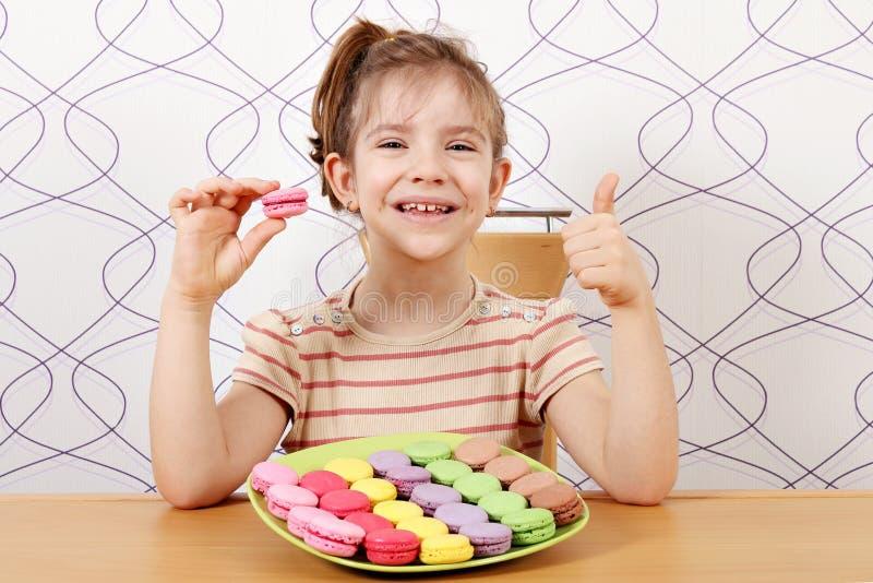 Μικρό κορίτσι με macaroons και τον αντίχειρα επάνω στοκ εικόνες