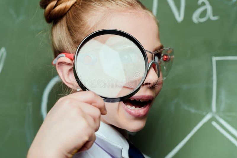Μικρό κορίτσι μορφασμού με την ενίσχυση - γυαλί με τον πίνακα κιμωλίας πίσω στοκ εικόνα