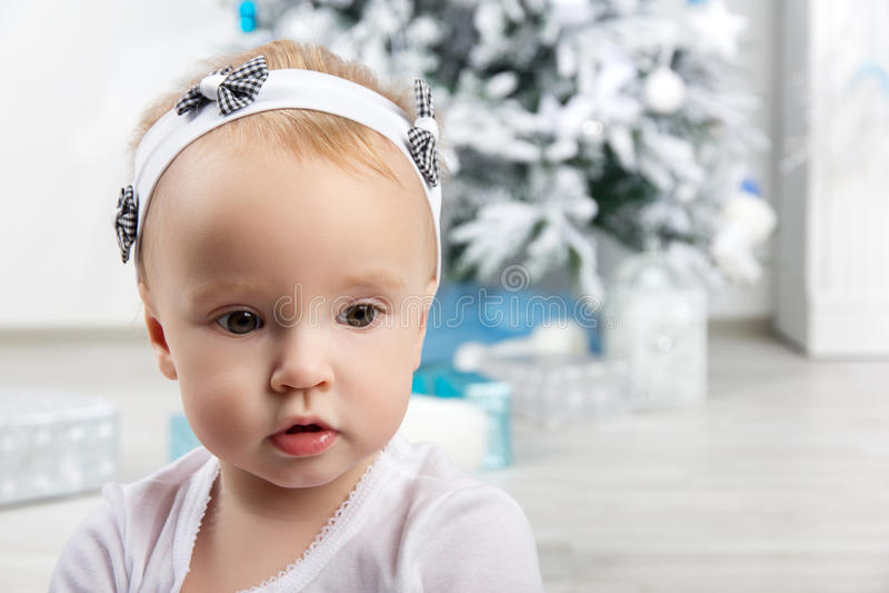 Μικρό κορίτσι μπροστά από το χριστουγεννιάτικο δέντρο που κοιτάζει λοξά στοκ εικόνες