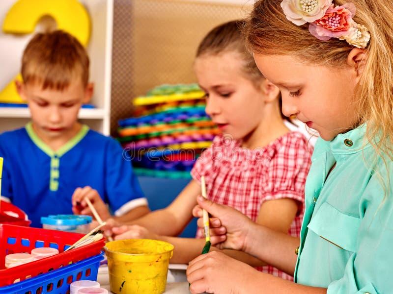 Μικρό κορίτσι ομάδας με τη βούρτσα που χρωματίζει μέσα στοκ φωτογραφία με δικαίωμα ελεύθερης χρήσης