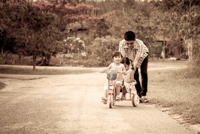 Μικρό κορίτσι παιδιών που έχει τη διασκέδαση για να οδηγήσει το τρίκυκλο με την οικογένεια στοκ φωτογραφίες με δικαίωμα ελεύθερης χρήσης
