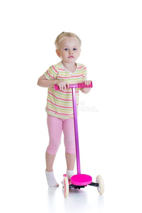 Μικρό κορίτσι παιδιών που οδηγά ένα μηχανικό δίκυκλο που απομονώνεται στο άσπρο υπόβαθρο στοκ εικόνα