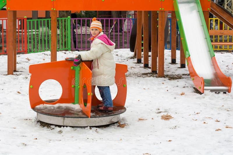 Μικρό κορίτσι που έχει τη διασκέδαση στη χειμερινή παιδική χαρά στοκ φωτογραφίες