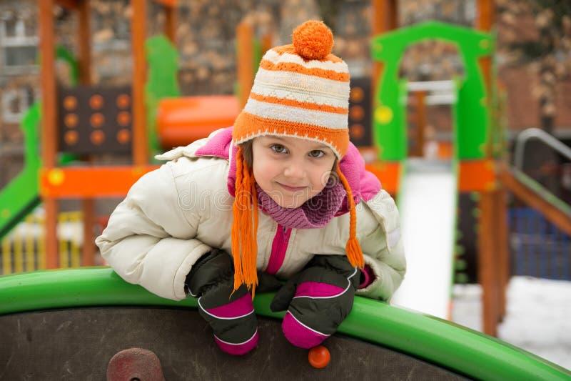 Μικρό κορίτσι που έχει τη διασκέδαση στη χειμερινή παιδική χαρά στοκ εικόνες