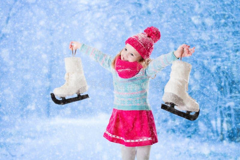 Μικρό κορίτσι που έχει τη διασκέδαση στον πάγο που κάνει πατινάζ το χειμώνα στοκ εικόνα