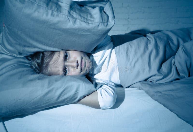 Μικρό κορίτσι που έχει τον ύπνο προβλήματος που κρατά τη νύχτα το μαξιλάρι το κεφάλι και τα αυτιά της που ανατρέπονται που καλύπτ στοκ φωτογραφία με δικαίωμα ελεύθερης χρήσης