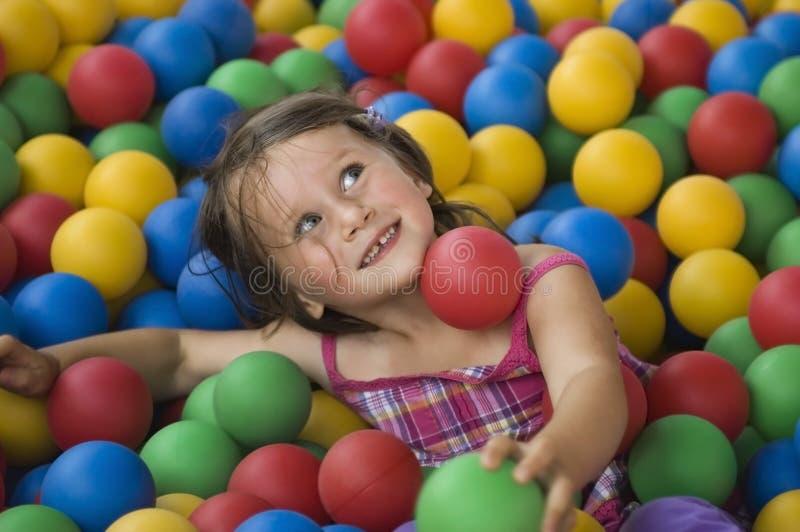 Μικρό κορίτσι που έχει το χρόνο διασκέδασης στη λίμνη σφαιρών στοκ φωτογραφίες