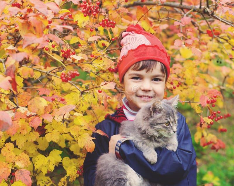 Μικρό κορίτσι που αγκαλιάζει μια γάτα στον κήπο στοκ εικόνες με δικαίωμα ελεύθερης χρήσης