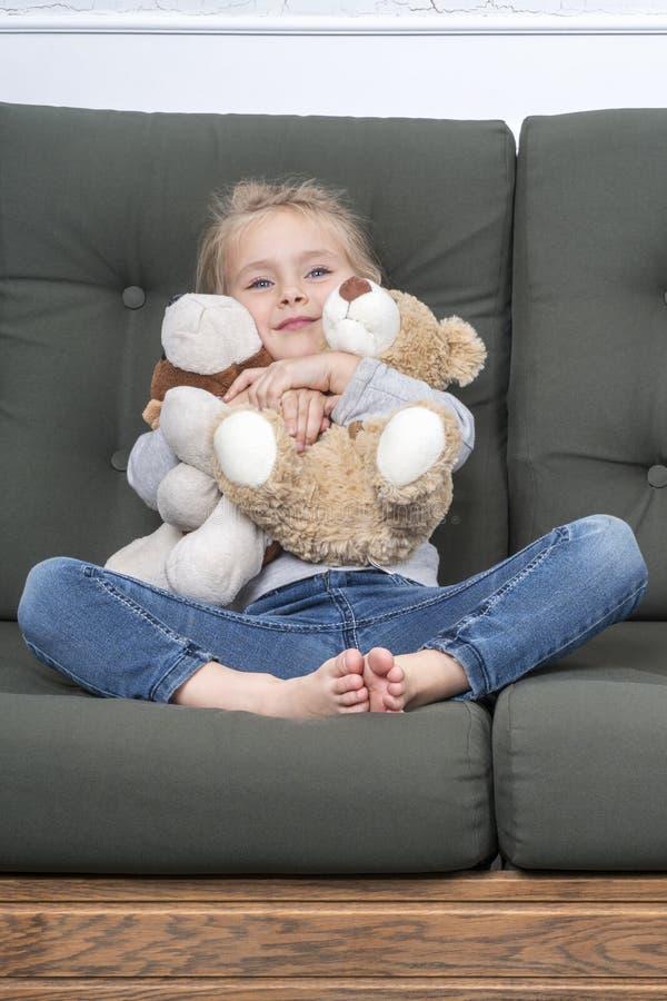 Μικρό κορίτσι που αγκαλιάζει τα παιχνίδια στοκ εικόνες με δικαίωμα ελεύθερης χρήσης