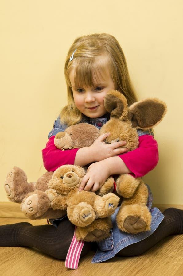 Μικρό κορίτσι που αγκαλιάζει τα γεμισμένα ζώα στοκ φωτογραφία