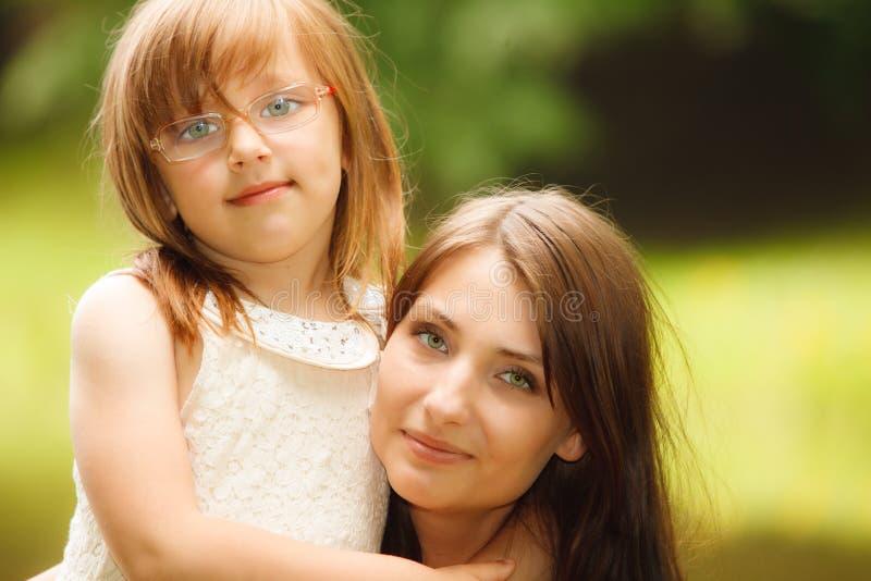Μικρό κορίτσι που αγκαλιάζει τη μητέρα του που εκφράζει τα τρυφερά συναισθήματα Αγάπη στοκ φωτογραφία