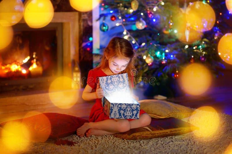 Μικρό κορίτσι που ανοίγει ένα μαγικό δώρο Χριστουγέννων στοκ εικόνες