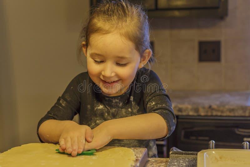 Μικρό κορίτσι που αποκόπτει τα μπισκότα στοκ φωτογραφίες