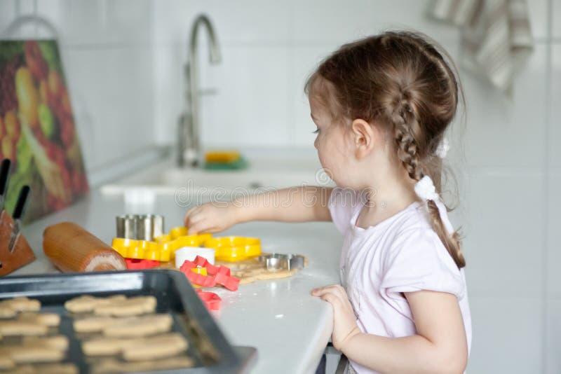 Μικρό κορίτσι που αποκόπτει τα μπισκότα στοκ εικόνες
