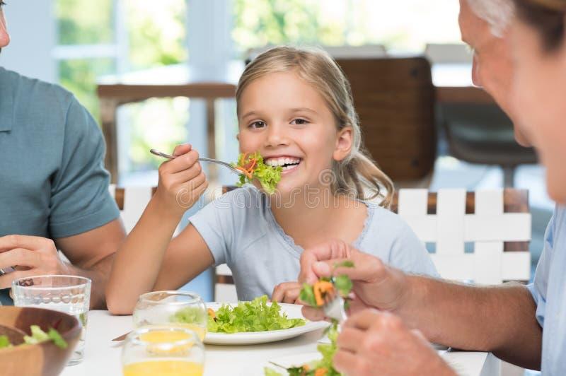 Μικρό κορίτσι που απολαμβάνει το μεσημεριανό γεύμα στοκ εικόνα