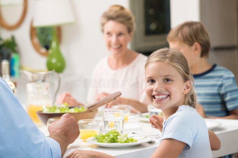 Μικρό κορίτσι που απολαμβάνει το μεσημεριανό γεύμα στοκ φωτογραφία