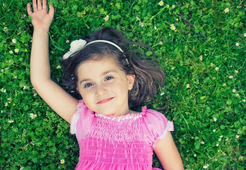 Μικρό κορίτσι που βάζει στη χλόη στοκ φωτογραφίες