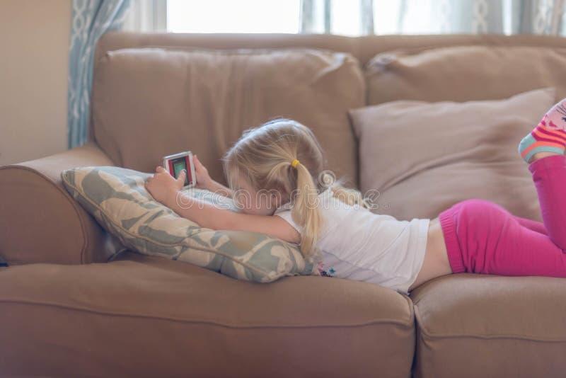 Μικρό κορίτσι που βάζει στο στομάχι της στον καναπέ καθιστικών στοκ εικόνα