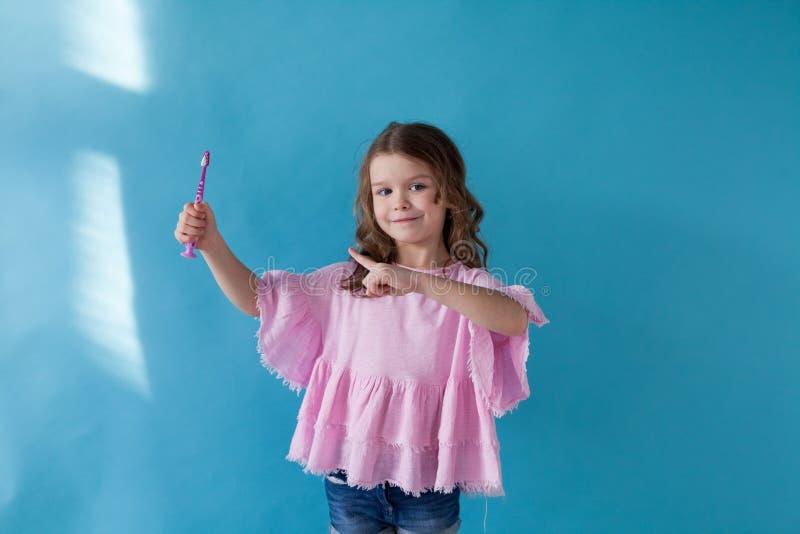 Μικρό κορίτσι που βουρτσίζει τα δόντια του με ένα ζούλιγμα οδοντοβουρτσών στοκ φωτογραφίες